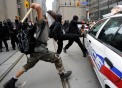 An anarchist vandalized a police cruiser on Bay Street before setting it on fire Saturday, June 26, 2010. Lucas Oleniuk-Toronto Star